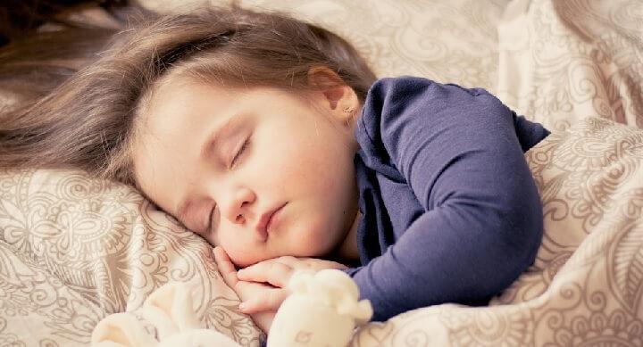 Trött litet barn sover i hotellsängen